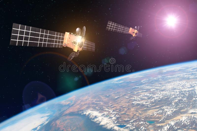 Group space satellite orbiting the earth and bright lights sun reflected from solar panels. Elements of this image furnished by. NASA royalty free stock photography