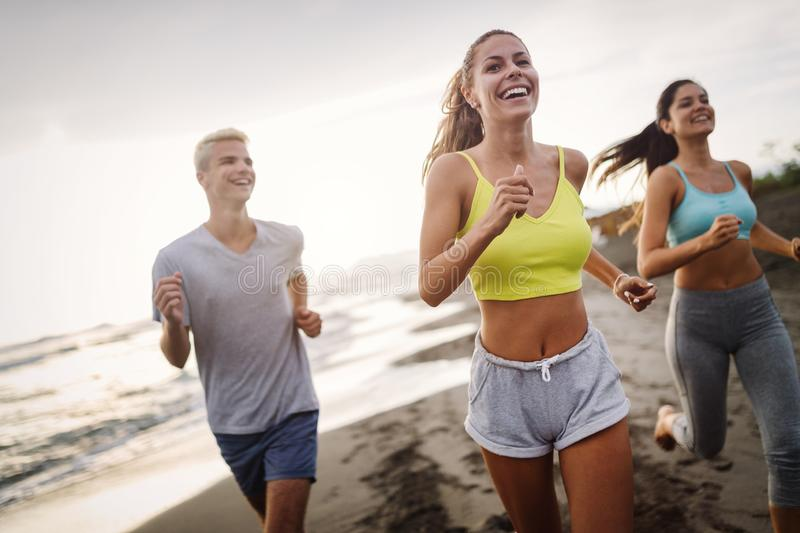 Group of sport people running on the beach stock photo