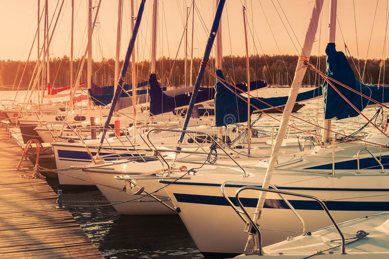 Sailing yachts docked by the wooden pier at sunset stock photography