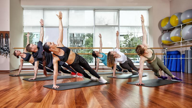 A group of sporting young people in sportswear, in a fitness room, doing push-ups or planks in the gym. Group fitness. Concept, group workouts, motivation royalty free stock image