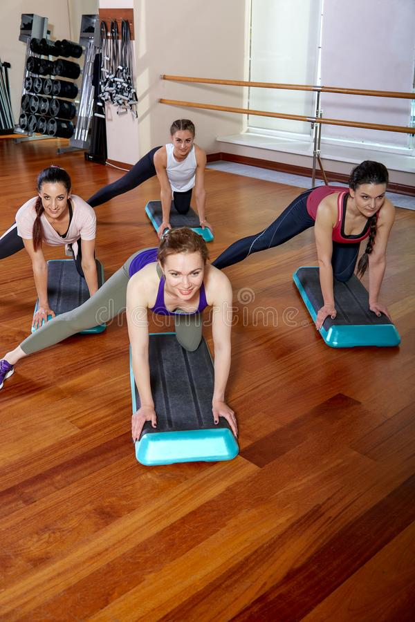 A group of sporting young people in sportswear, in a fitness room, doing push-ups or planks in the gym. Group fitness. Concept, group workouts, motivation royalty free stock photos