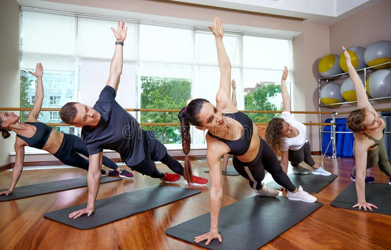 A group of sporting young people in sportswear, in a fitness room, doing push-ups or planks in the gym. Group fitness. Concept, group workouts, motivation stock photos