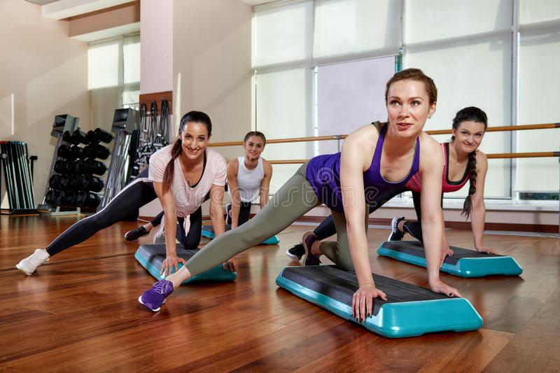 A group of sporting young people in sportswear, in a fitness room, doing push-ups or planks in the gym. Group fitness. Concept, group workouts, motivation stock image