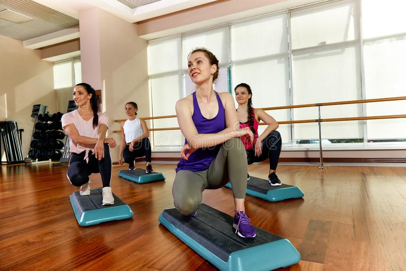 A group of sporting young people in sportswear, in a fitness room, doing push-ups or planks in the gym. Group fitness. Concept, group workouts, motivation stock photography