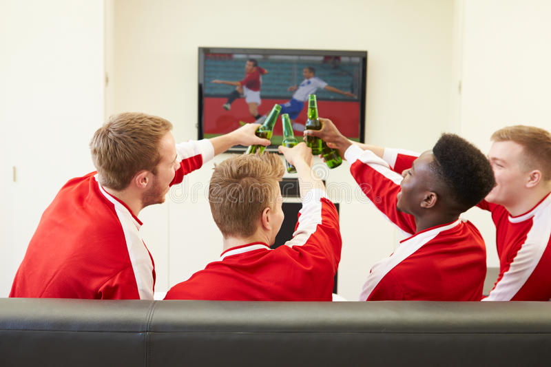 Group Of Sports Fans Watching Game On TV At Home stock image