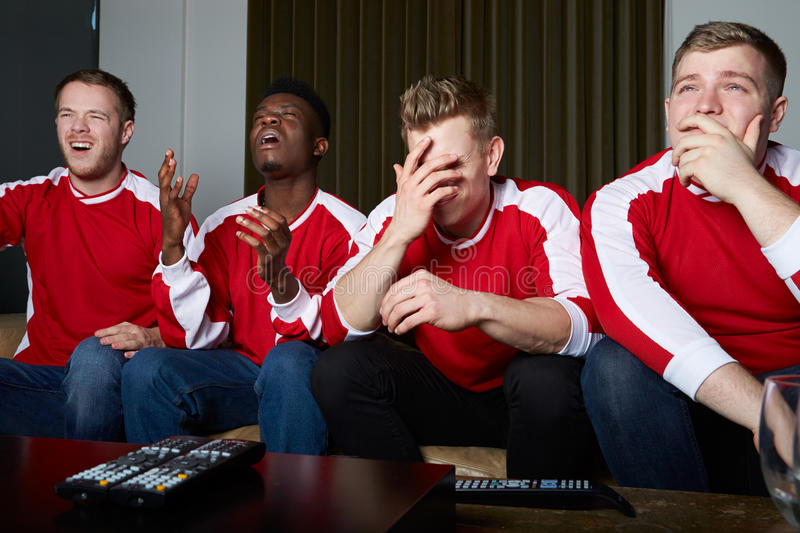 Group Of Sports Fans Watching Game On TV At Home stock photography