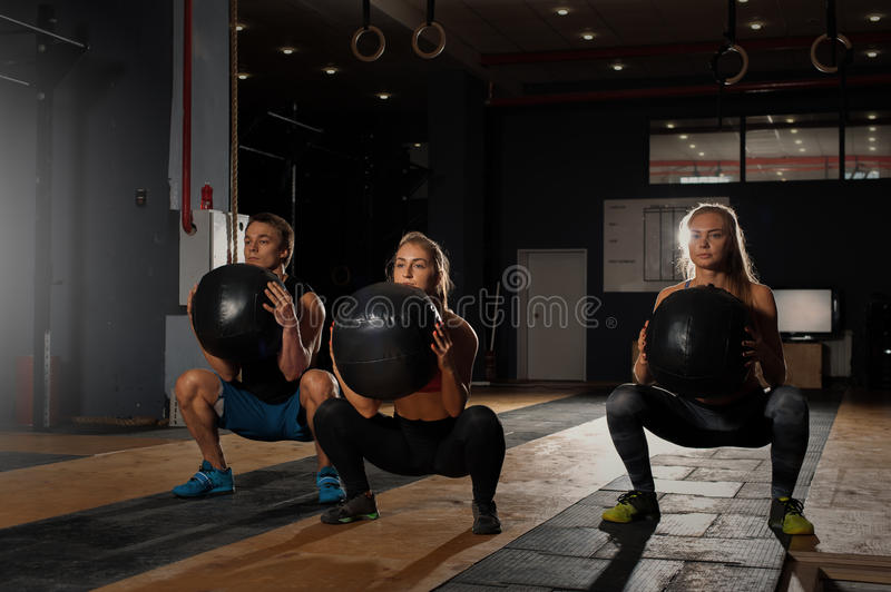 Group of sporty caucasian adults exercising in gym. Athletes doing squats with weights. Fitness, sports concept royalty free stock image