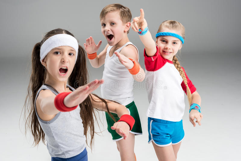 Group of sporty children in sportswear exercising together on grey. Children sport concept stock photos