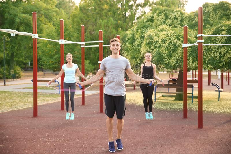 Group of sporty people jumping rope on athletic field outdoors stock photography