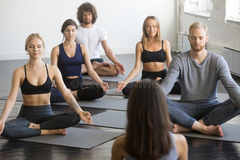 Group of sporty people in Lotus exercise with female instructor royalty free stock images