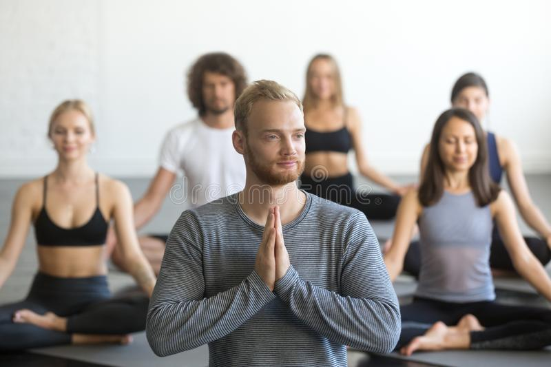 Group of sporty people in Lotus exercise with male instructor stock photo