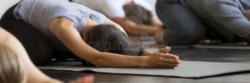 Sporty girls guys practicing Child exercise doing Balasana yoga pose royalty free stock images