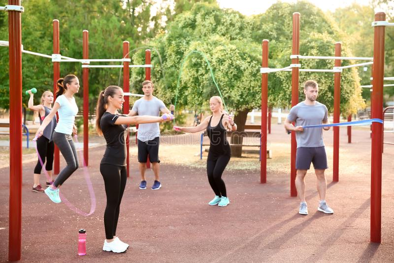 Group of sporty people training on athletic field outdoors stock photography