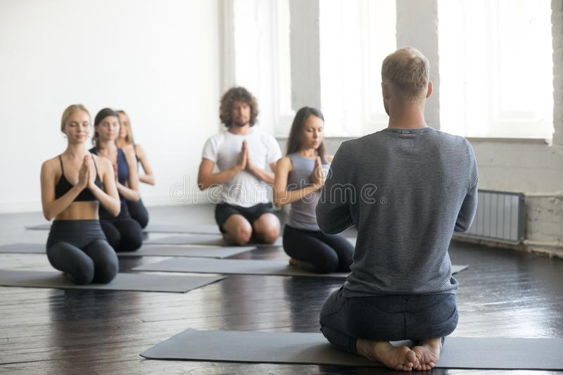 Group of sporty people in vajrasana exercise with instructor royalty free stock photo