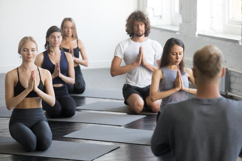 Group of sporty people in vajrasana exercise royalty free stock photography