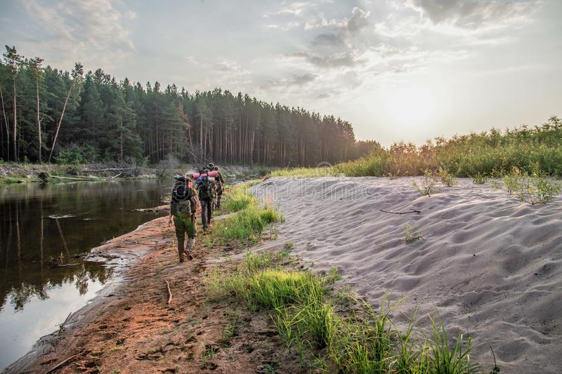 A group of hikers with backpacks travel near the river in Chernobyl zone stock photography