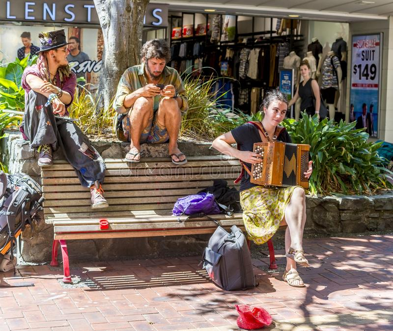 Group of street musicians playing the accordion and sitting on a bench in a street in Wellington stock images