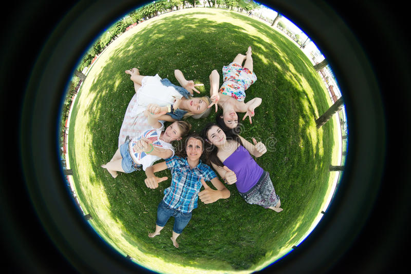 Group student on bench outdoor. Grupa students lie on the grass, photographed by fisheye royalty free stock photography