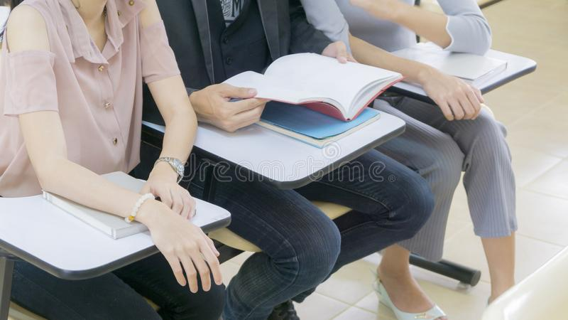 Group student read book and sit in classroom stock image