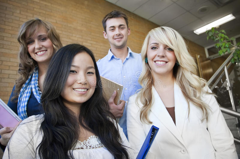 Group of Students. Four young, attractive students walking down the stairway at school stock images