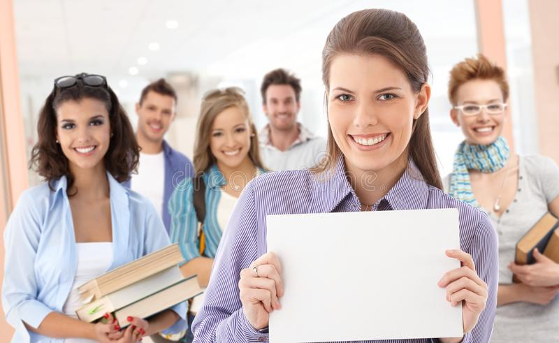 Group of students with blank sheet for copyspace. Group of students on school corridor. Girl in front holding blank sheet, paste your text there royalty free stock photography