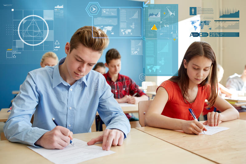 Group of students with books writing school test. Education, learning, statistics and people concept - group of students with books writing school test over royalty free stock photo