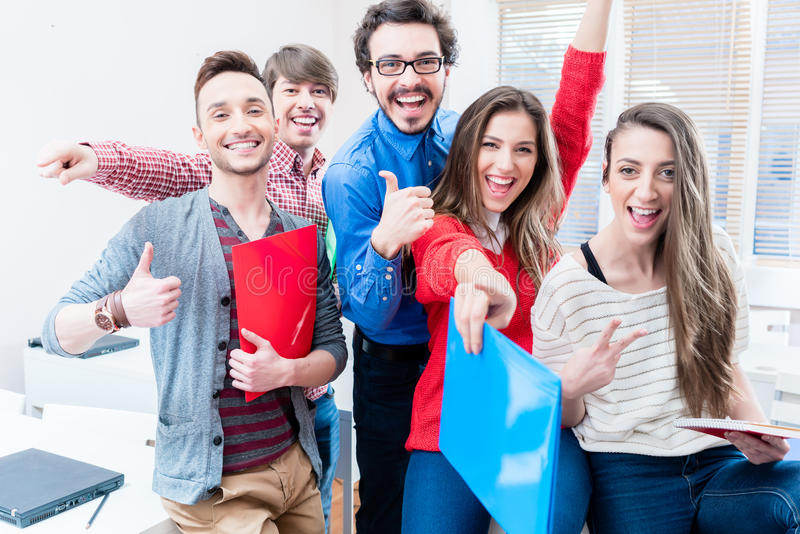 Group of students celebrating success in exams. Being cheerful throwing arms up royalty free stock photography