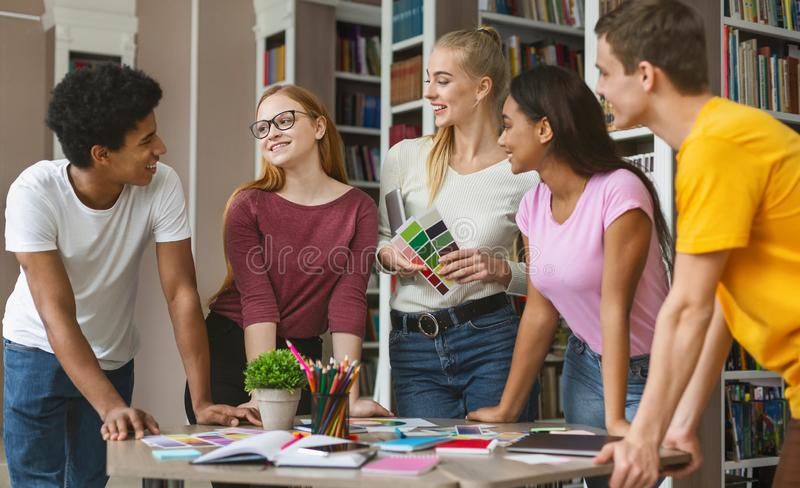 Group of students choosing color for future project. Group of multinational students staying at library and choosing color for future project, having fun while stock image