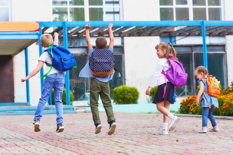 A group of students happily jump around the school. Boys and girls happy return to primary school. back to school. the first day of autumn. day of knowledge royalty free stock image