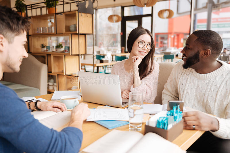 Group of students having conversation at cafe royalty free stock image