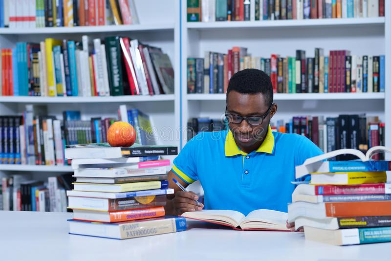 Male african american college student reading in library stock photo