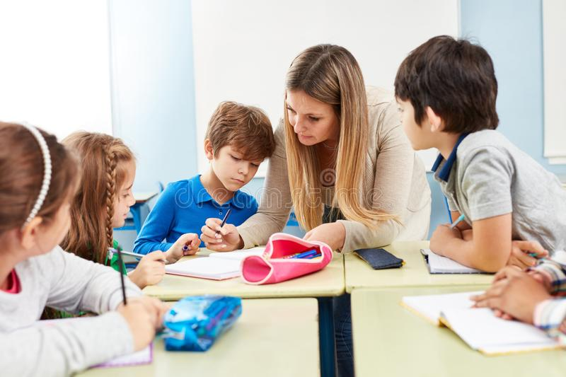 Group of students learns with the help of a teacher stock photos