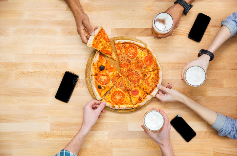 Group of students meeting and eating pizza together royalty free stock photo