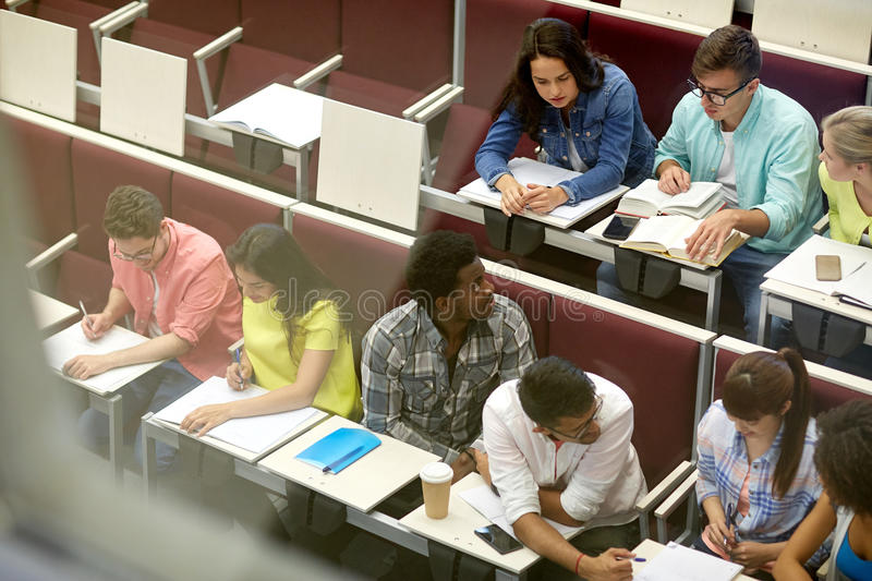 Group of students with notebooks at lecture hall stock photo