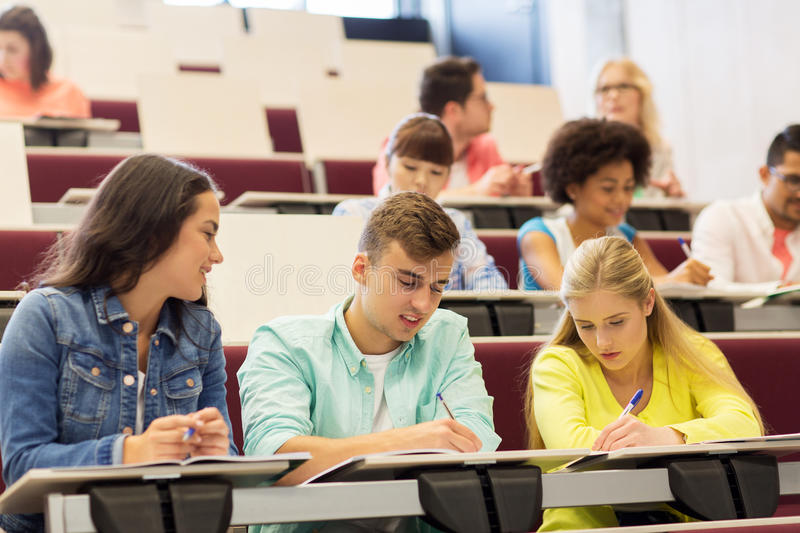Group of students with notebooks in lecture hall stock images
