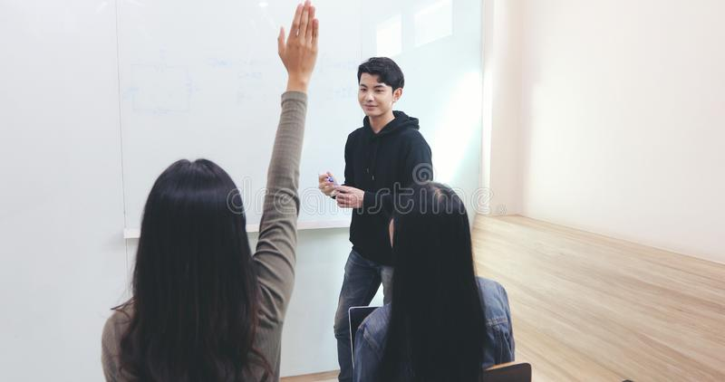 Group Students raise their hands to ask a friend questions for teaching at whiteboard in classroom stock image
