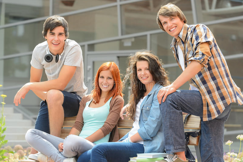 Group of students sitting bench front college stock images