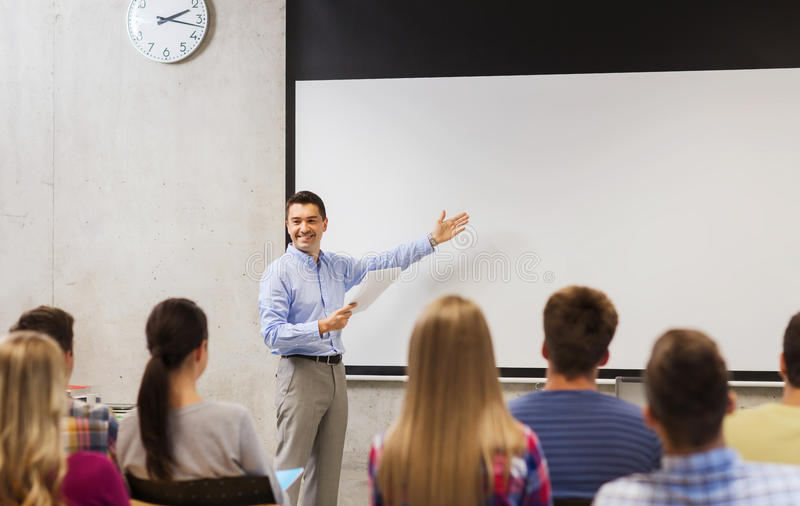 Group of students and smiling teacher with notepad. Education, high school, technology and people concept - smiling teacher with notepad, laptop computer stock photo