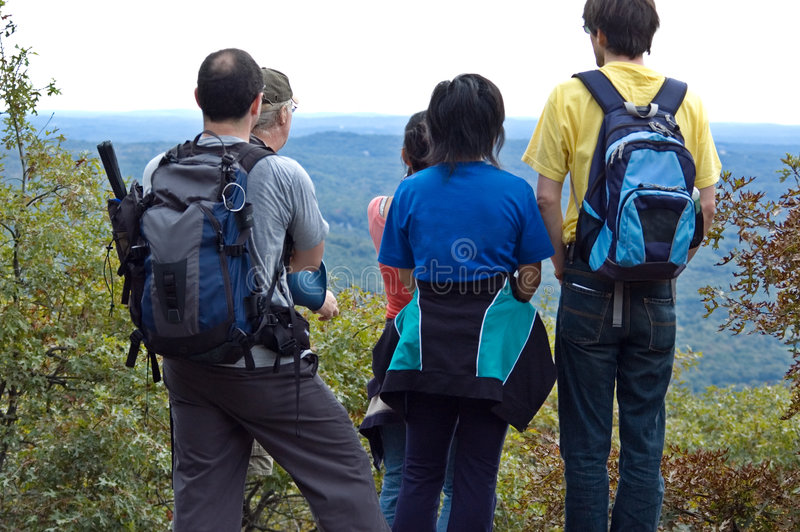 Group of students standing on the mountain top royalty free stock photography