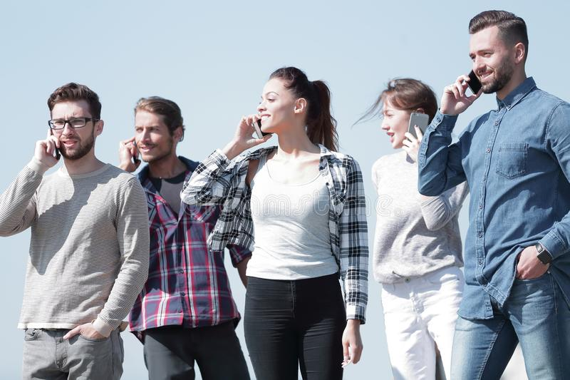 Group of students talking on their smartphones. stock images