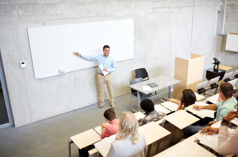 Group of students and teacher at lecture. Education, high school, university, teaching and people concept - group of international students and teacher with royalty free stock photography