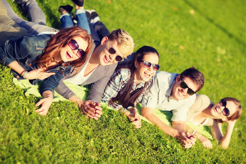 Group of students or teenagers lying in park royalty free stock photo