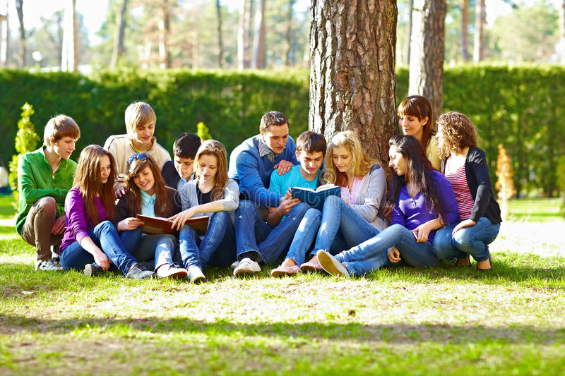 Group of students under the tree. Group of students with books under the tree on the grass stock image