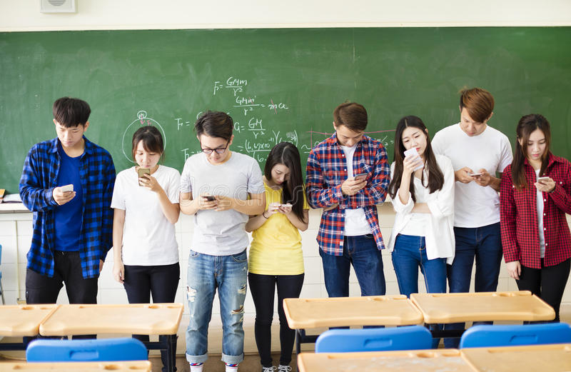 Group of students using smart mobile phones in classroom royalty free stock image