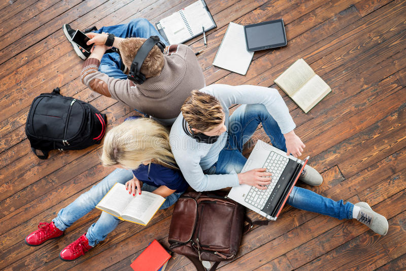 Group of students using smartphones, laptops and reading books. In headphones listening to the music and leaning on each other on wooden floor having notebooks royalty free stock photo