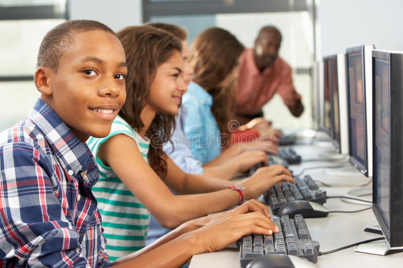 Group Of Students Working At Computers In Classroom. Looking At Camera Smiling stock photography