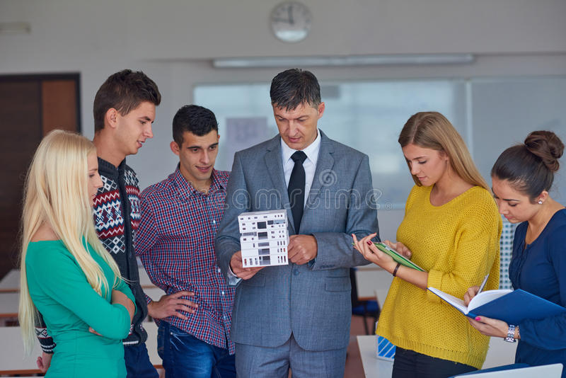 Group of students working with teacher on house model. Group of students working with teacher on wooden small house model royalty free stock image