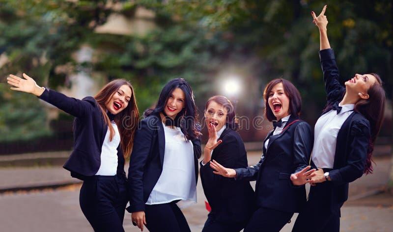 Group of stylish happy women on evening street stock photo