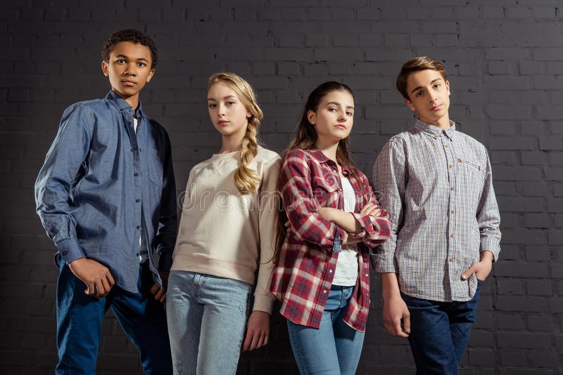 group of stylish teenagers standing together in front of black stock photography