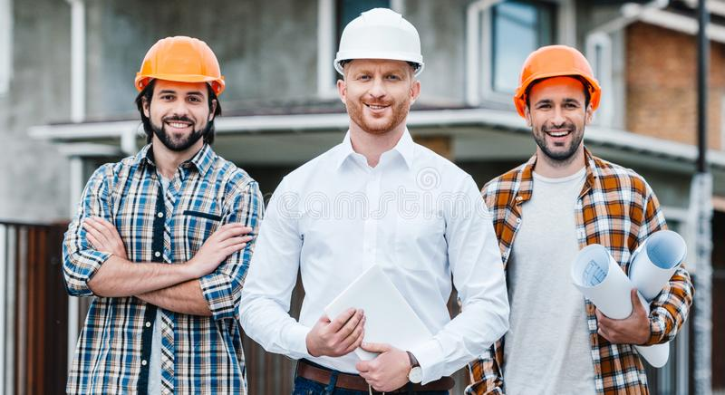 Group of successful architects in hard hats looking at camera in front of. Building house stock photography